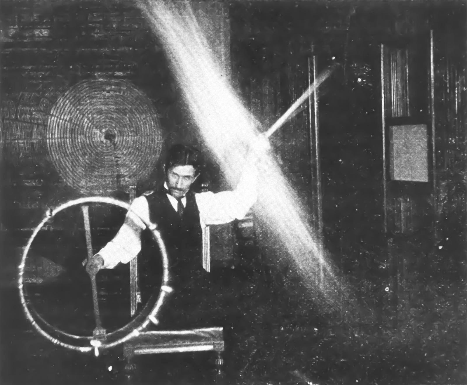 Tesla-e`ksperimentiruet-s-tokami-vyisokogo-napryazheniya-i-vyisokoy-chastotyi.-Tok-prohodit-cherez-ego-telo-zazhigaet-lampu-v-levoy-ruke-i-ne-prinosit-vreda-uchyonomu